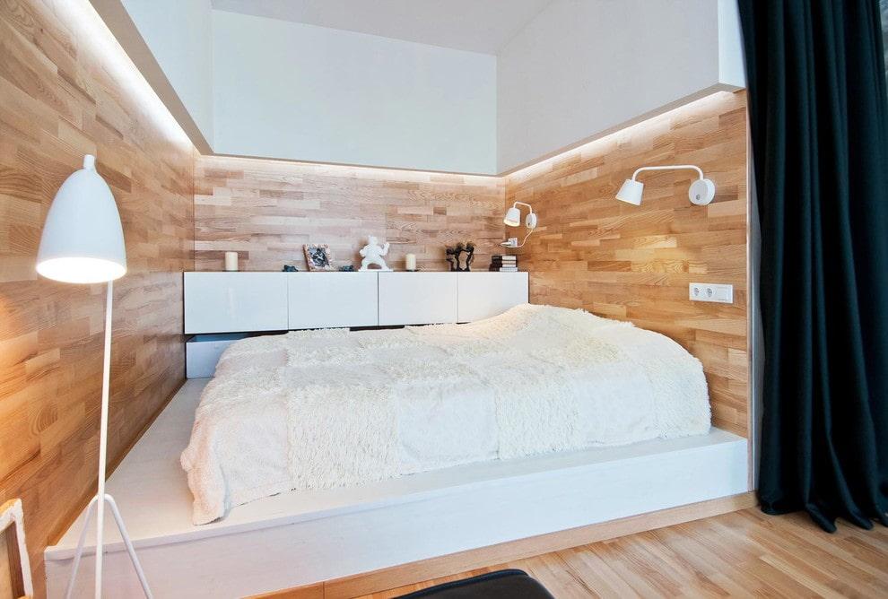 Маленькая комната с кроватью на подиуме из бетона