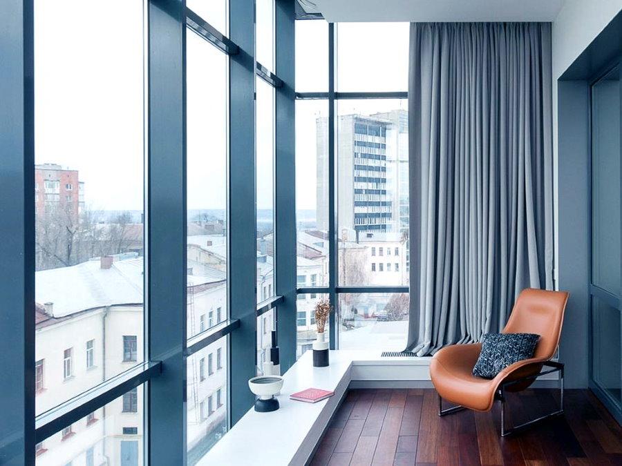 Кожаное кресло на балконе с большими окнами
