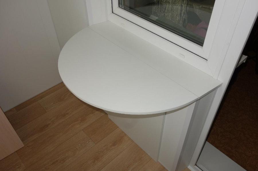 Откидной столик из пластика под окном на балконе