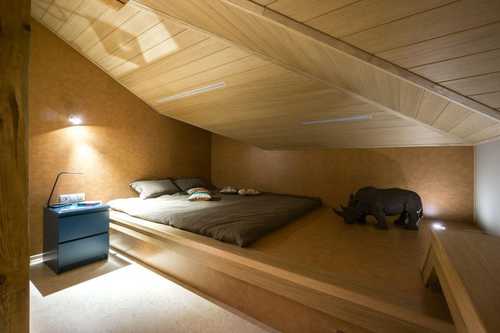 Низкий подиум с кроватью в спальне на мансарде