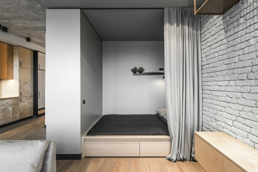 Подиум с кроватью в нише стены квартиры-студии