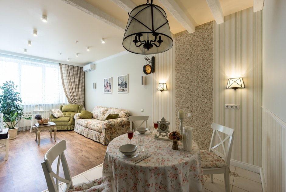 Обеденный столик с красивой скатертью в кухне-гостиной