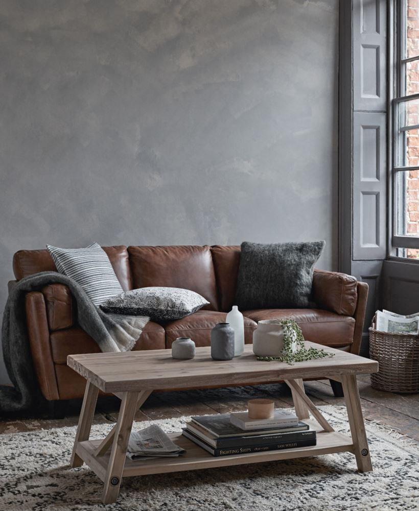 Коричневый диван у стены серого цвета
