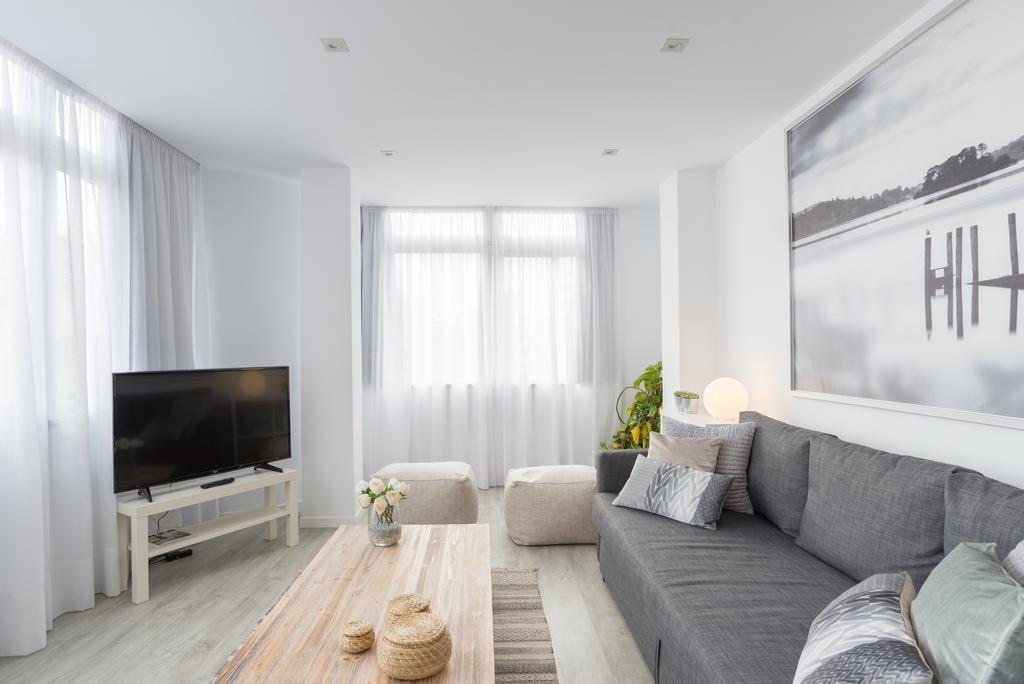 Интерьер белой гостиной с двумя окнами