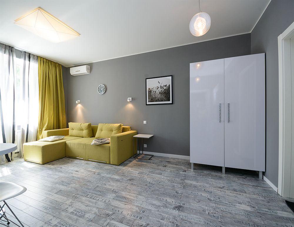 Горчичный диван на сером ламинате в комнате