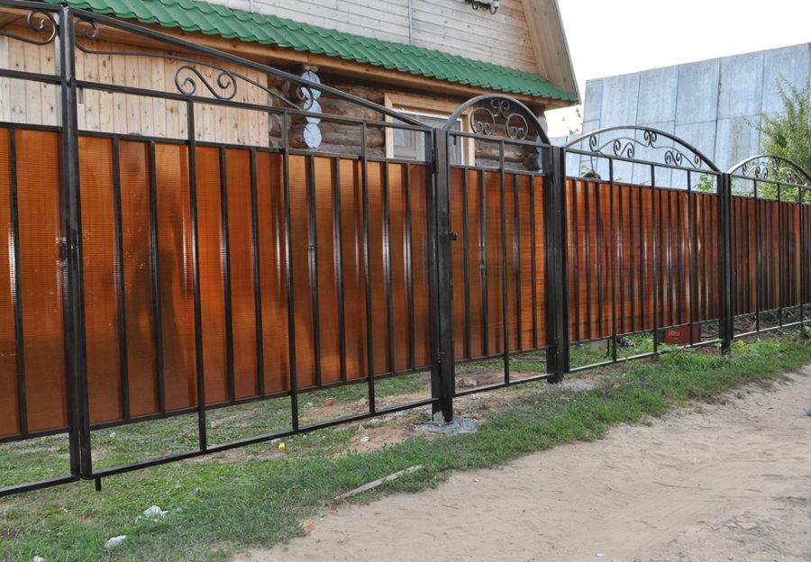 Оранжевый поликарбонат на садовом заборе