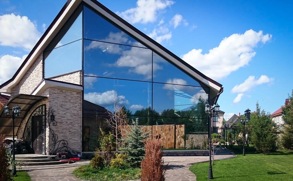 Отделка фасада дома стеклопанелями с отражающей поверхностью