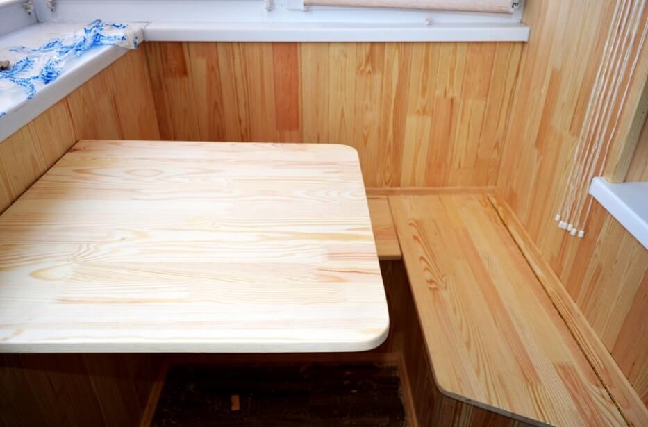 Откидной столик у лавочки с деревянной отделкой