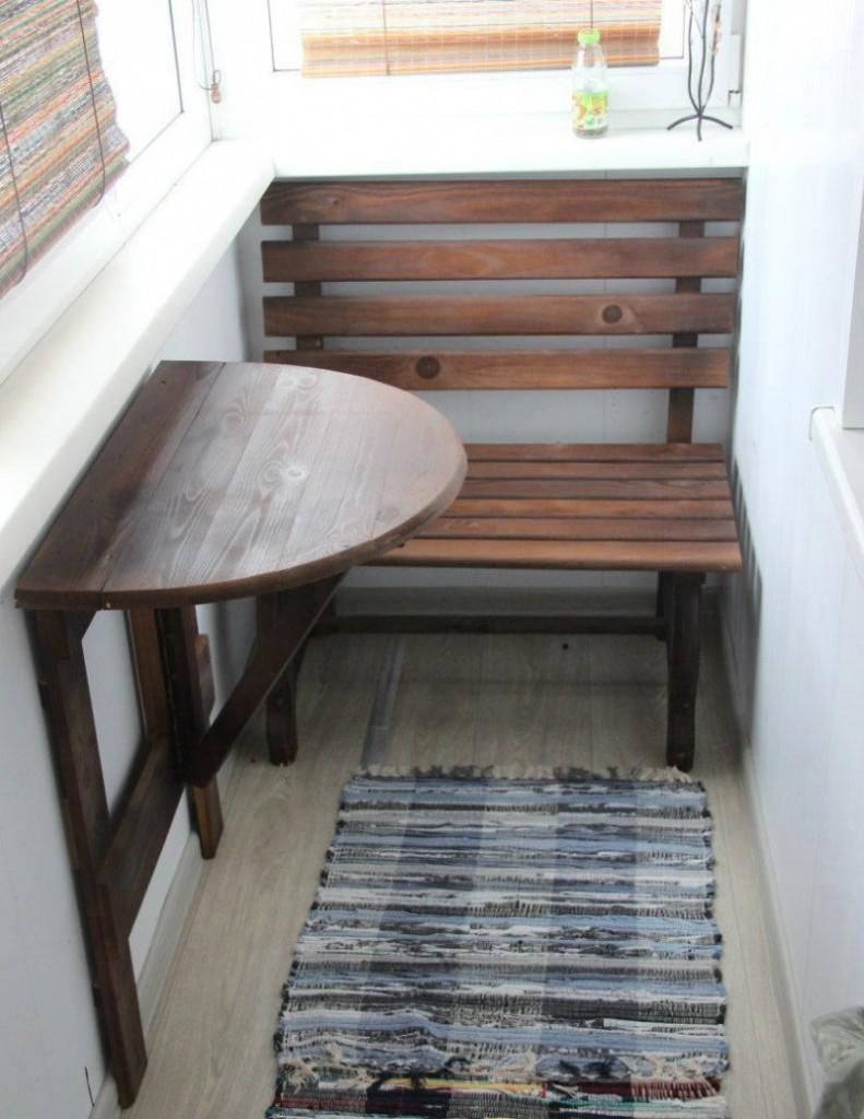 Деревянная скамейка возле откидного столика на балконе