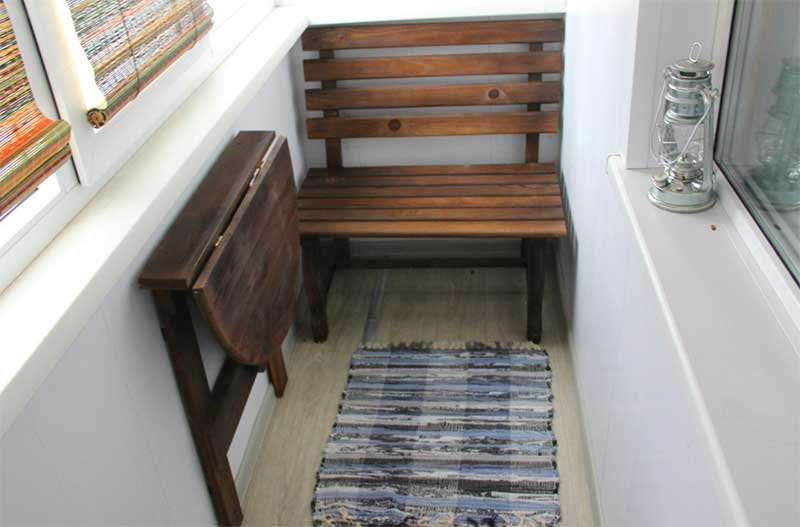 Откидной столик из дерева на стене лоджии