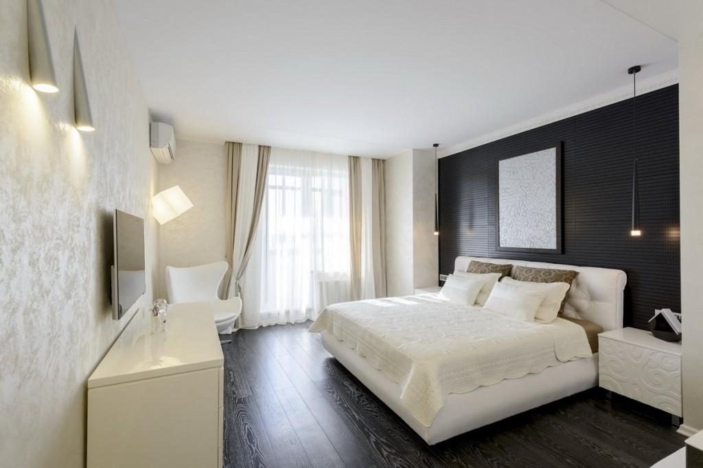Белая кровать в спальне с темным полом
