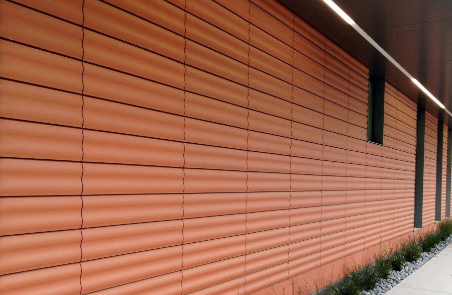 Волнистая поверхность терракотовых панелей на фасаде дома