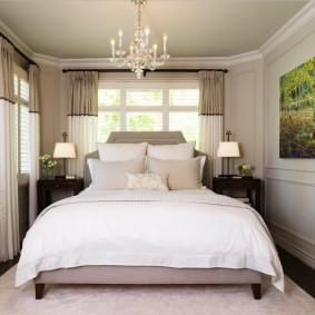 Интерьер узкой спальни с двумя окнами
