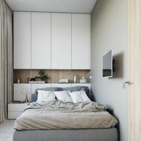 Двухспальная кровать вдоль стены в узкой спальне