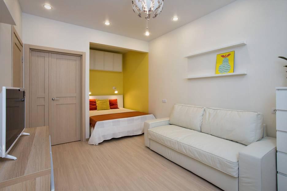 Желтые стены узкой ниши с кроватью