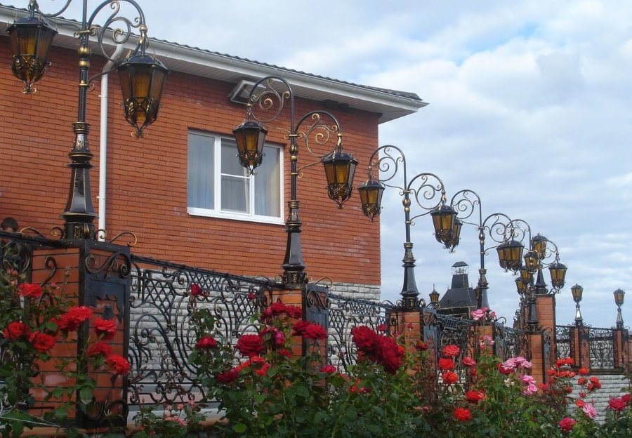 Садовые фонари на кирпичных столбах забора