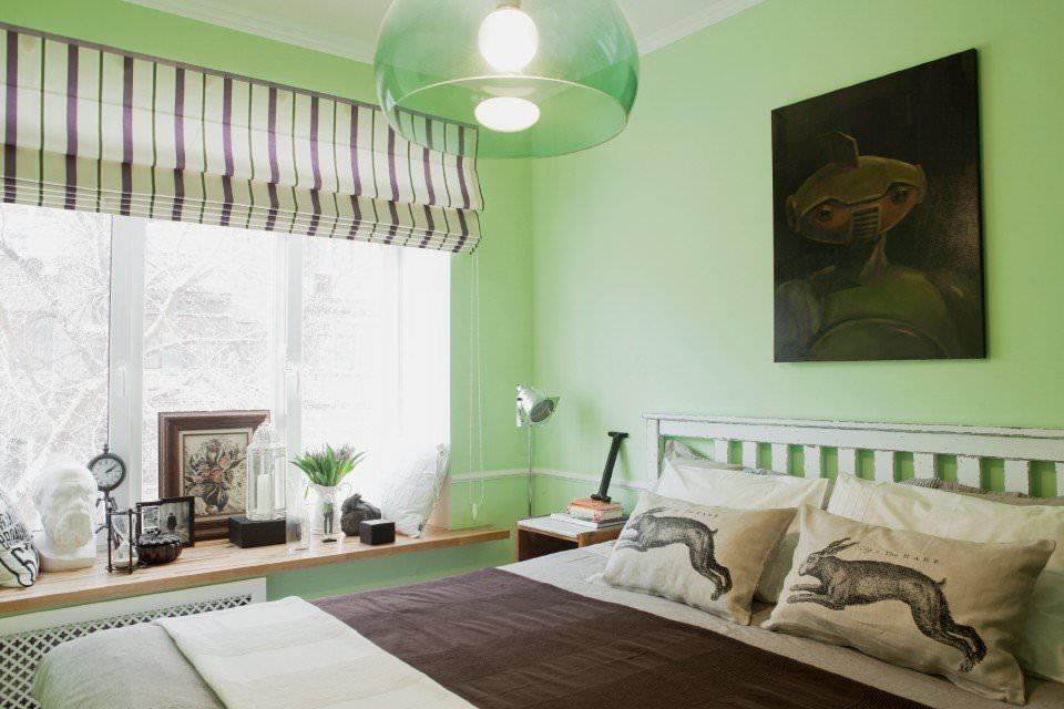 Двухспальная кровать в спальне с зелеными стенами