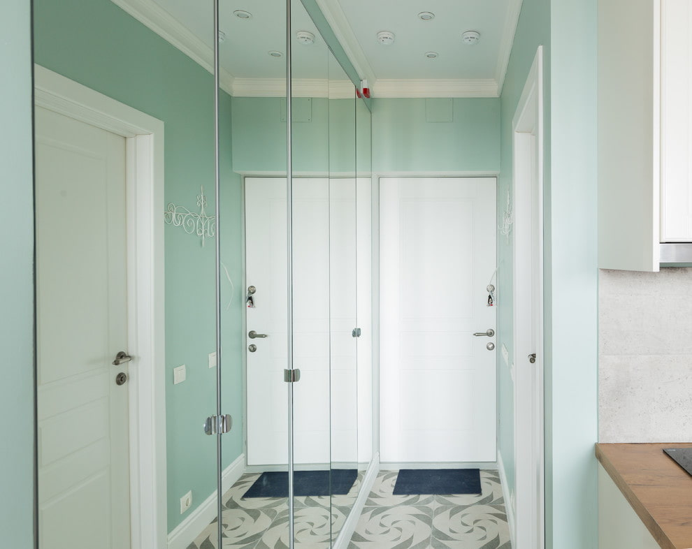 Зеркальные двери шкафов в узком коридоре квартиры