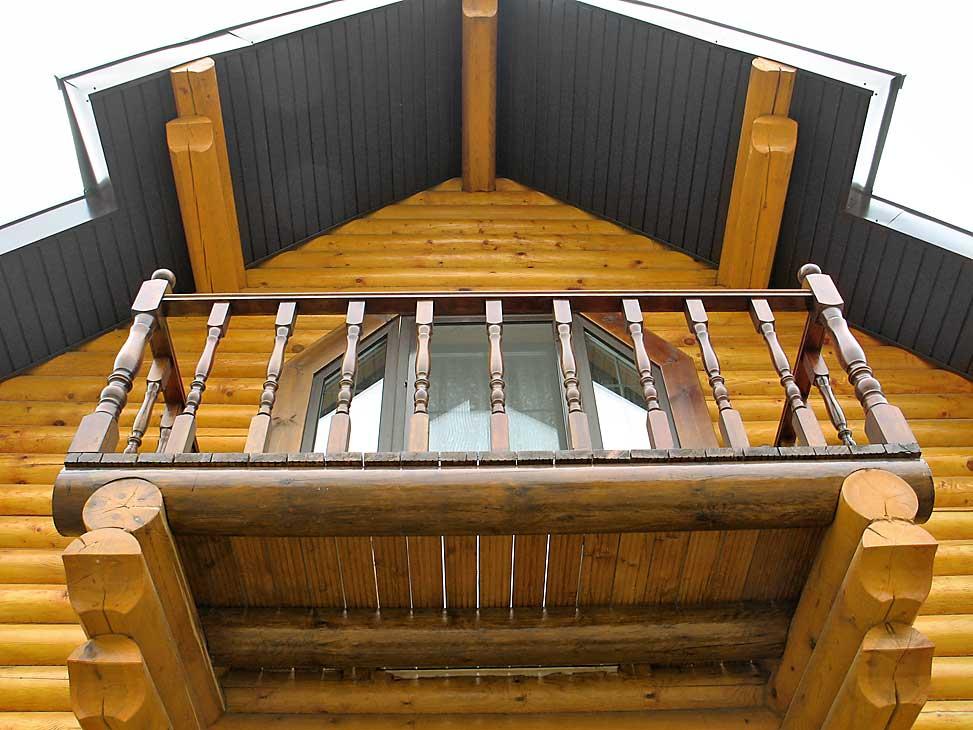 Открытый балкон на фасаде бревенчатого дома