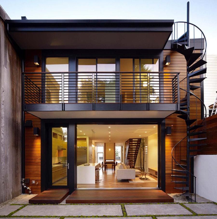Металлический балкон над входом в загородный дом
