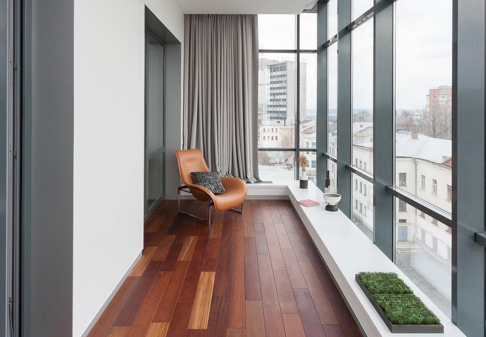 Кожаное кресло на балконе с серыми шторами