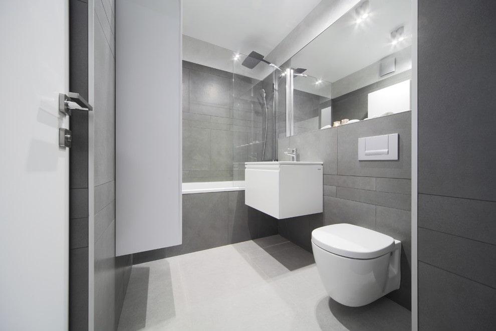 Белый подвесной унитаз на светло-серой стене ванной