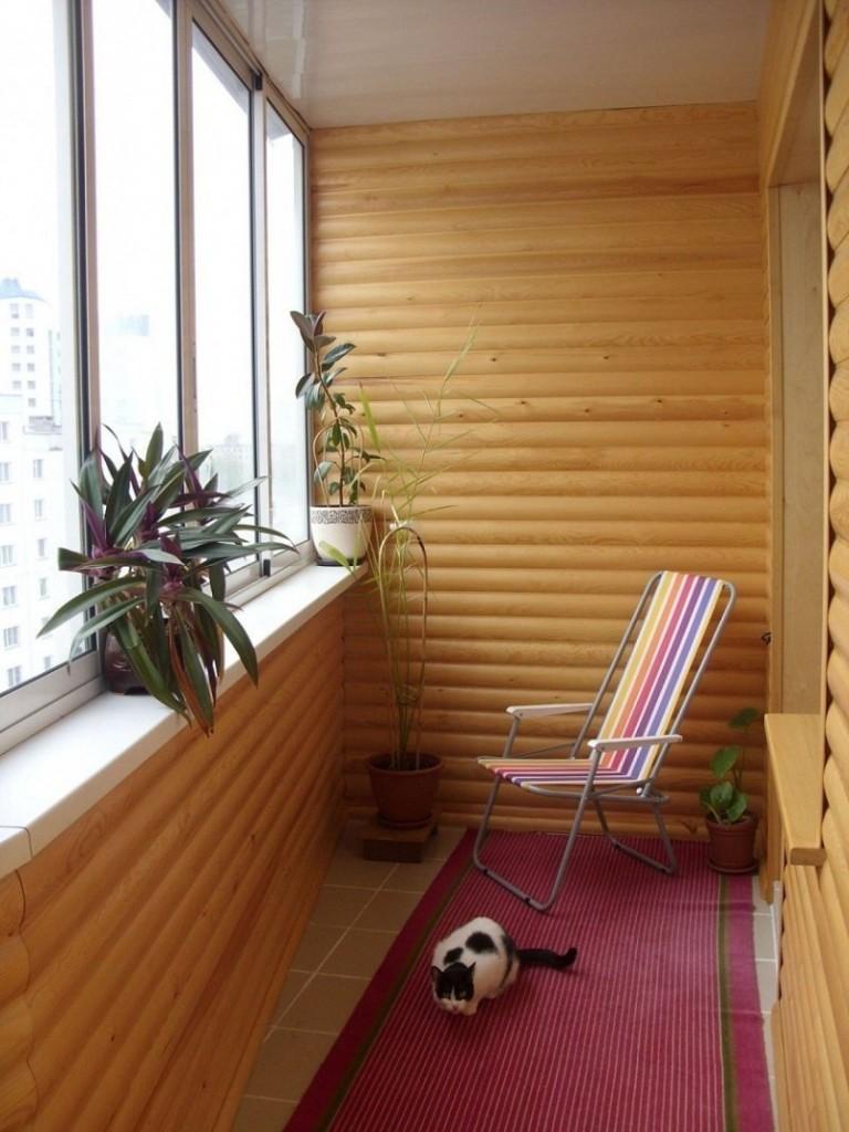 Складной стульчик на лоджии с деревянной отделкой