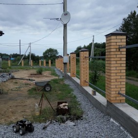 Кирпичные столбы на бетонном фундаменте забора