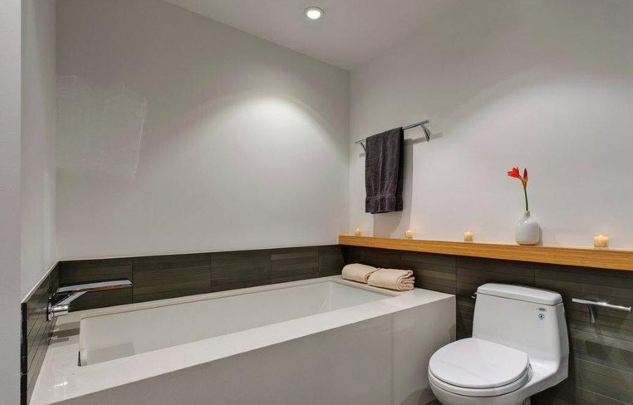 Красный цветок на деревянной полочке в ванной