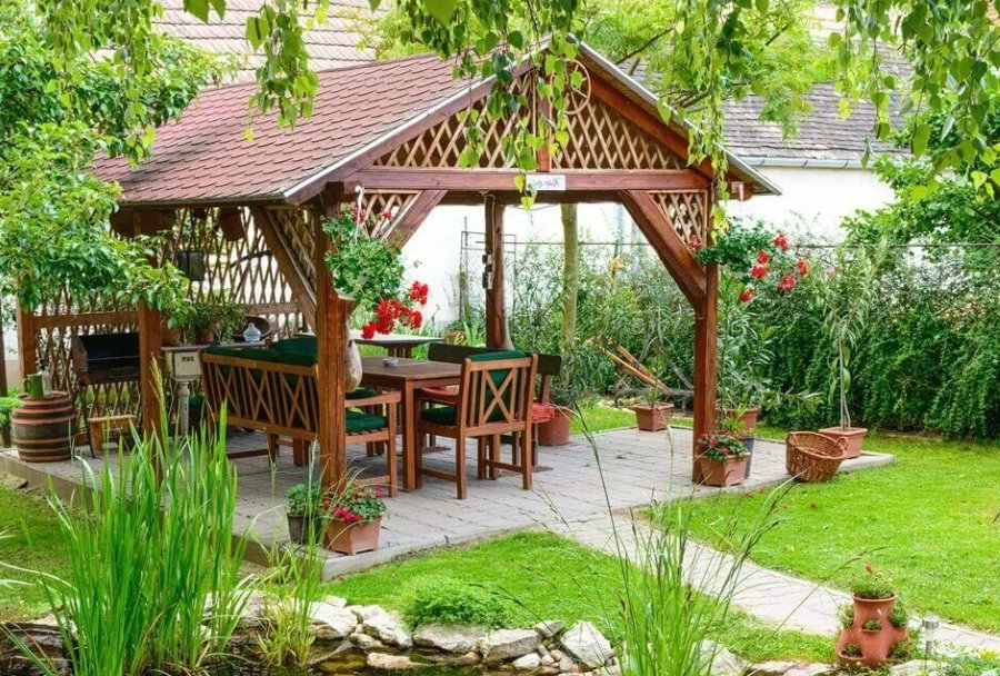Красивая деревянная беседка в ландшафте садового участка