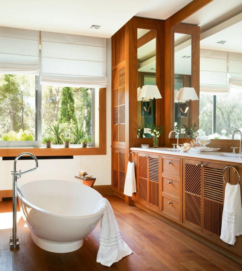 Деревянная мебель в ванной частного дома с окном