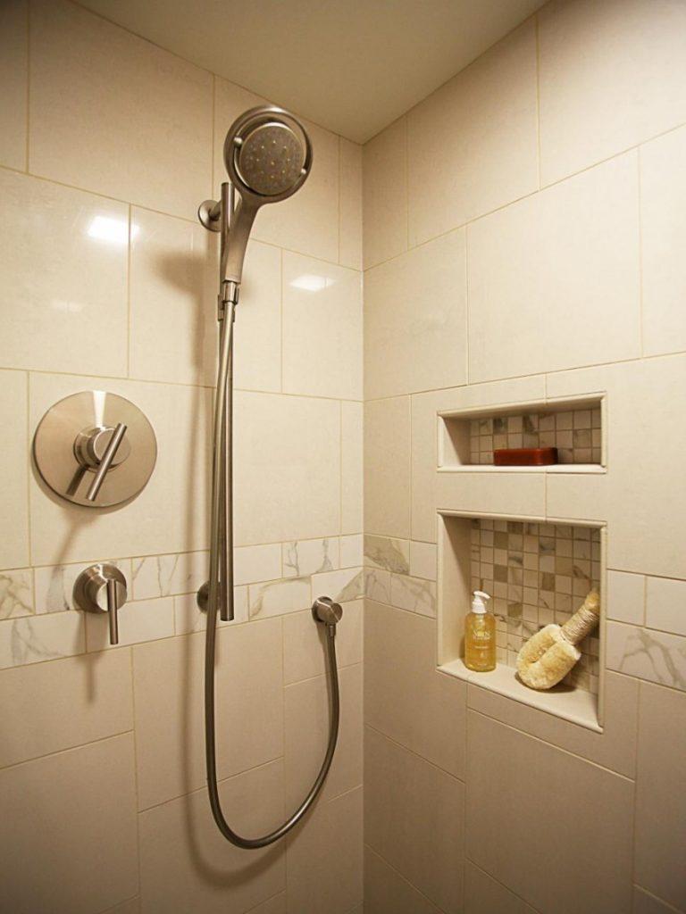 Душевая лейка на стене ванной комнаты