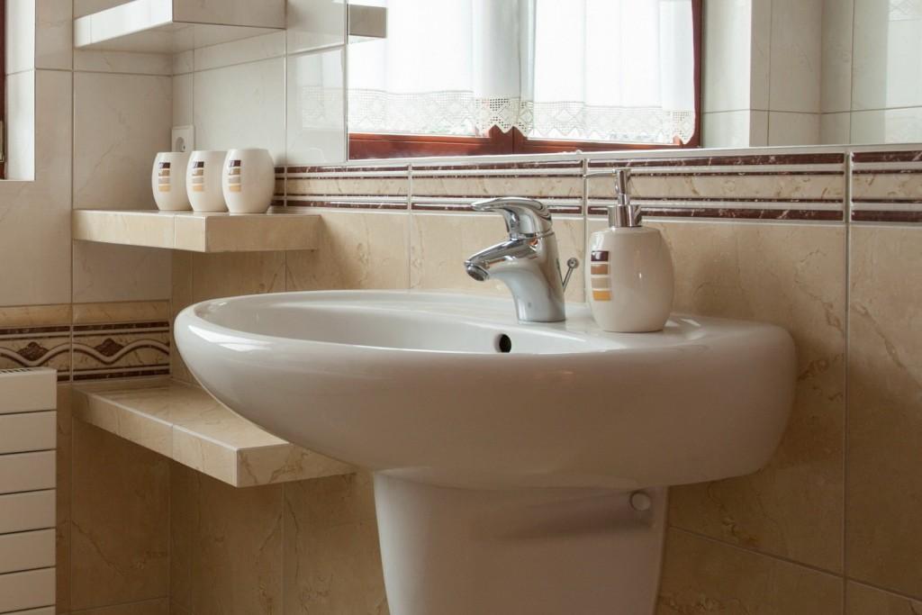 Фаянсовая раковина в ванной с бежевой плиткой