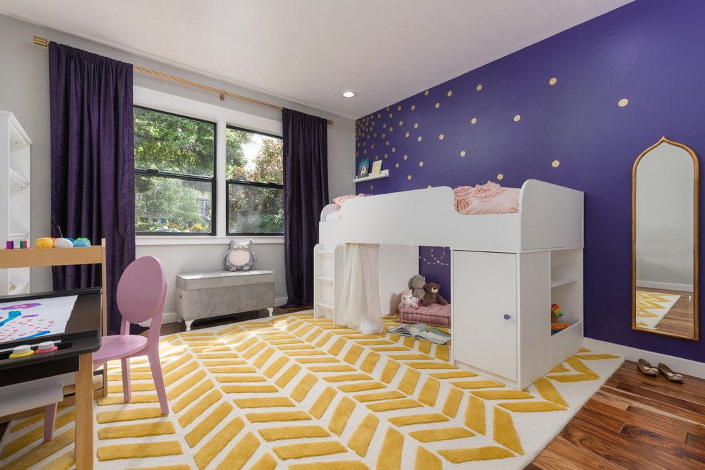 Высокая детская кровать на фоне стены фиолетового цвета