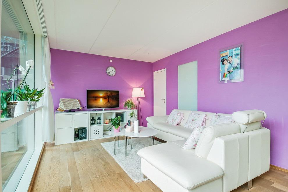 Белый угловой диван у светло-фиолетовой стены