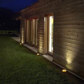 Подсветка деревянной стены дома грунтовыми светильниками