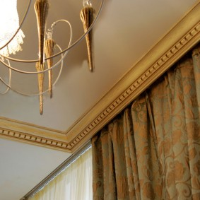 Золотистый багет под потолком комнаты