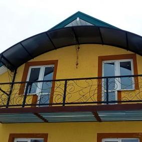 Металлический балкон на желтой стене частного дома