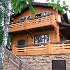 Балкон на стене двухэтажного дома из бруса