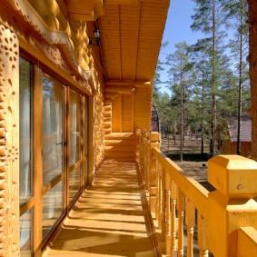 Длинный балкон вдоль стены деревянного дома
