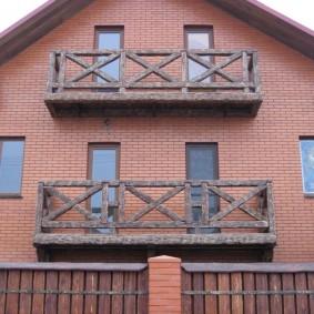 Балконы из дерева на доме из кирпича
