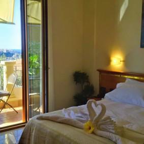 Панорамное окно в интерьере спальни с балконом