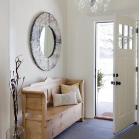 Деревянная скамейка со спинкой у двери в прихожей
