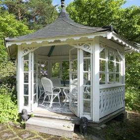 Белая беседка в саду пейзажного стиля