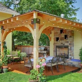 Садовая мебель в беседке на деревянных столбах