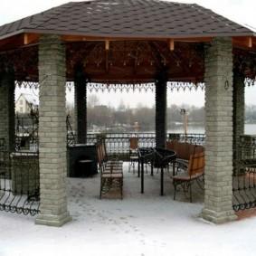 Садовая мебель в открытой беседке восьмиугольной формы