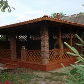 Беседка с деревянными перилами между кирпичными столбами