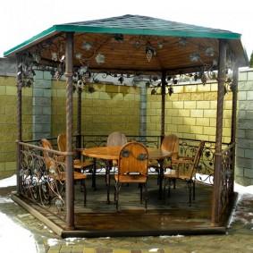 Деревянная мебель внутри небольшой беседки