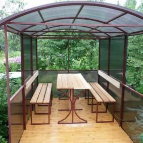 Садовая мебель внутри небольшой беседки