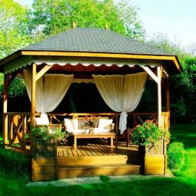 Белые шторы в беседке с деревянным полом
